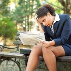 upset businesswoman newspaper park