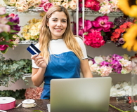Florist holding a credit card in her flower shop