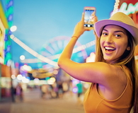 Happy girl is taking pictures with her mobile phone