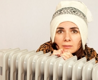Woman freezing near her heater