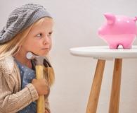 Little girl looking at piggy bank