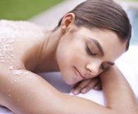 Woman using best body scrubs for clear skin