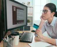 Woman sitting in front of working computer