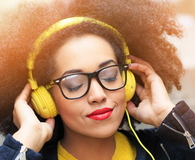 Young woman listening music on yellow headphones