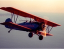 vintage biplane in flight over seascape at sunset