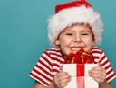 Little boy excitedly holds Christmas gift