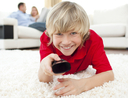 Boy holding a remote control watching TV
