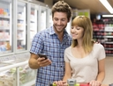 Couple using their phone to save at the grocery store