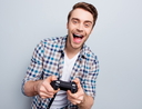 Excited guy in checkered shirt holding joystick