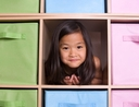 Little girl surrounded by organized storage boxes