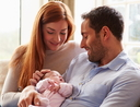 Mother And Father At Home With Newborn Baby
