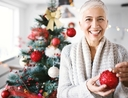 Woman decorating Christmas tree during holiday season