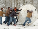 Guys pushing a giant snowball