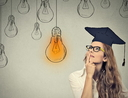 Thoughtful graduate student woman looking at light bulb
