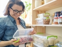 Woman adding food to her pantry