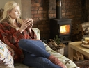 Woman keeping heating costs low with fireplace
