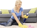 Woman using best allergen spray on carpet