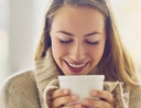 Woman holding mug of coffee feeling joy