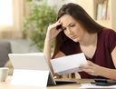 Worried woman calculating accountancy reading a letter