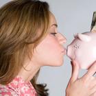 woman kissing piggy bank