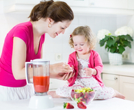 mother and daughter using blender making smoothies