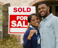 African American couple standing in front of new home