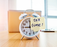 A clock with tax time sticky note