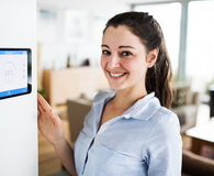 A woman looking at tablet with smart home screen
