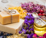 Bars of homemade soaps, honey or oil and healing herbs
