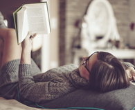 Beautiful young woman at home reading book