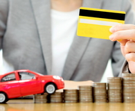 Businesswoman hold credit card, a toy car and a stack