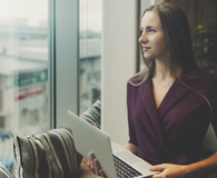 Businesswoman with laptop next to office window