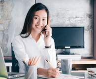 Businesswoman with smiling face talking on mobile