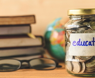 Coins in glass jar with education label