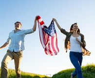 Couple holding amrican flag and running in field