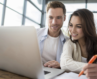 Young couple using investing software that is worth the cost