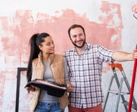 Couple doing paint job on old house