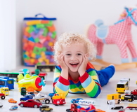 Curly little boy playing with toy cars