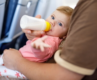 Dad holding his baby daughter during flight