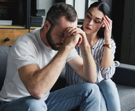 Depressed young couple sitting on couch at home