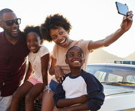 Family Posing For Selfie Next To Car