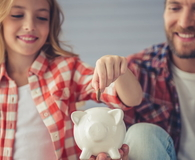 Father and daughter with piggy bank