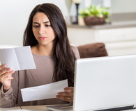 Frustrated woman paying bills at home