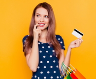Girl having bank card in hand and finger near lips