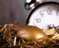 Gold and Golden Nest Egg with time clock on background