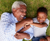 Grandfather and grandson play lying on grass