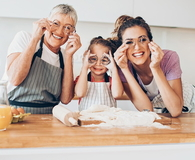 Grandmother, mother and daughter having fun in the kitchen