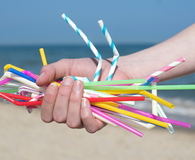 Hand Holding Plastic Straws Polluting Beach