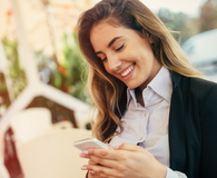 Happy businesswoman using phone