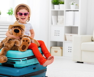 Happy child girl collect suitcase on vacation
